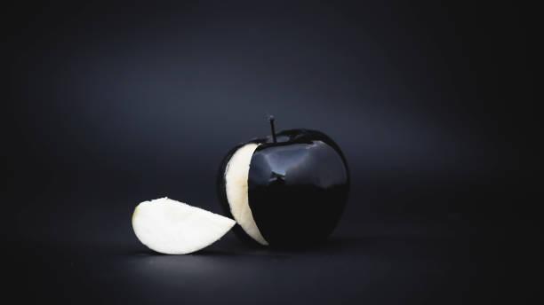 sliced black apple on a black background with a slice